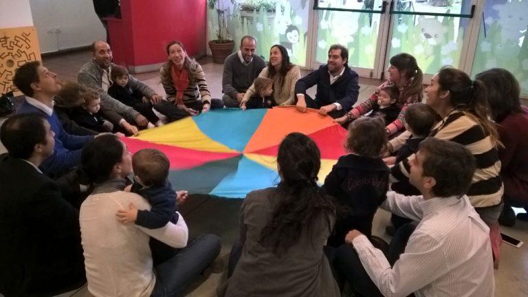 nursery open classes. familias sosteniendo manta de colores